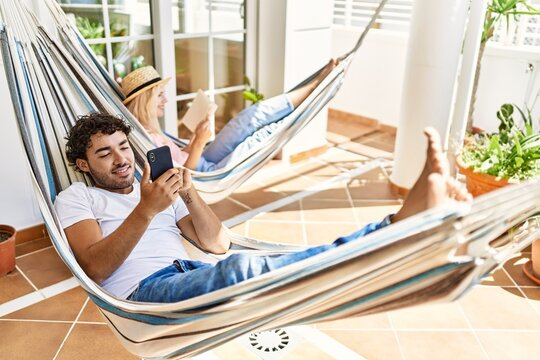 Young couple smiling happy relaxed using smartphone and reading book. Lying on hammock at terrace.