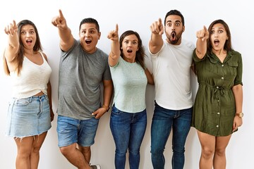 Fototapeta Group of young hispanic friends standing together over isolated background pointing with finger surprised ahead, open mouth amazed expression, something on the front obraz