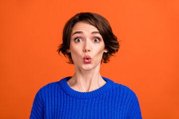 Photo of impressed brunette short hairdo lady wear blue sweater isolated on orange color background
