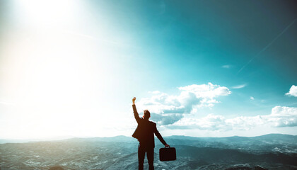 Obraz Silhouette of successful businessman keeping hands up hiking on the top of mountain - Celebrating success, winner and leader concept  - fototapety do salonu
