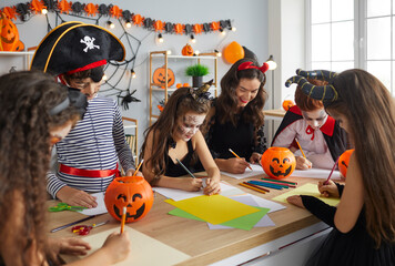 Fototapeta Arts and Crafts studio teacher doing creative activity with kids. Children dressed up as pirates, witches and vampires having fun Halloween party with their young English tutor at after school club obraz