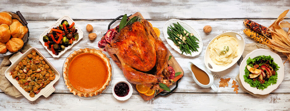 Traditional Thanksgiving turkey dinner. Above view table scene on a rustic white wood banner background. Turkey, mashed potatoes, stuffing, pumpkin pie and sides.