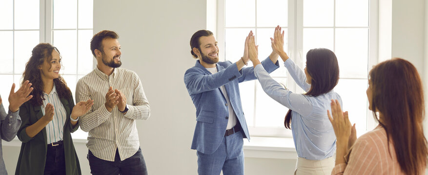 Two happy cheerful business people give each other a high five while colleagues are applauding. Team of people meeting in a modern office. Group of business partners making a deal. Teamwork concept