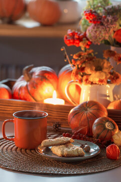 orange cup of tea and autumn decor with pumpkins, flowers and burning candles on table