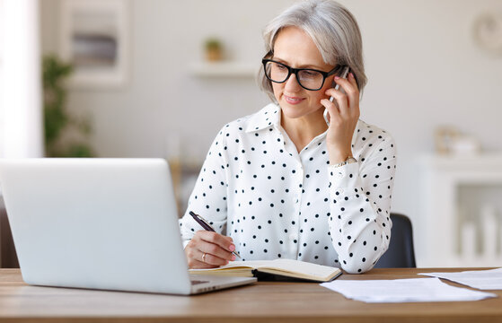 Focused senior business woman talking on mobile phone using laptop while working remotely at home