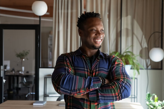 Head shot portrait of happy young African American business man, leader, self employed professional, startup developer. Thoughtful confident millennial hipster guy looking away in office, smiling