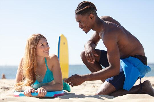 man teaching girlfriends how to do bodyboard