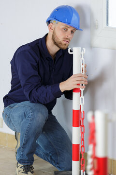 young male worker erecting safety chain around site