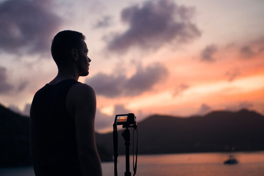 Young photographer with digital camera on tripod. Man photographing cosatline during colorful sunset. .