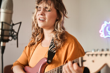 Woman playing guitar and singing in microphone