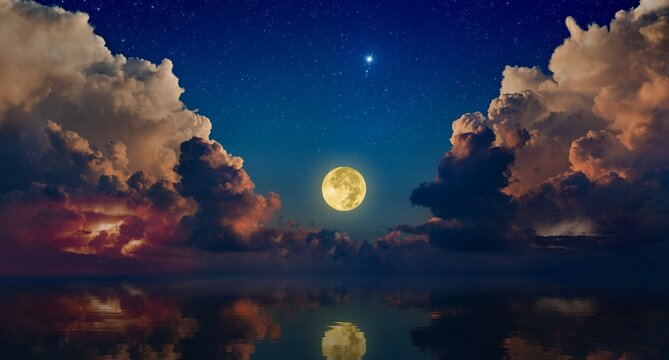 Full moon rising above serene sea in sunset sky with glowing clouds and bright stars