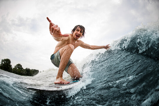 cheerful man show hand gesture riding on surf style wakeboard and touching the wave with one hand