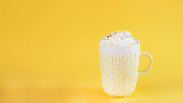 Pumpkin latte on yellow background in cozy mug. Image with copy space