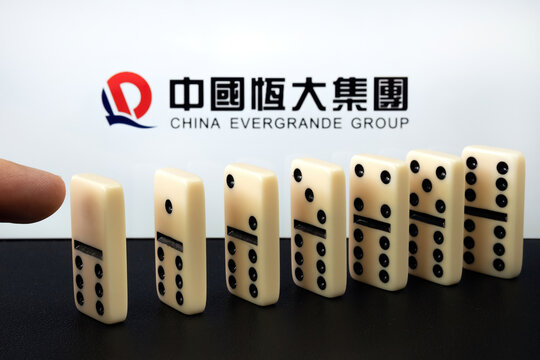 Domino blocks and blurred China Evergrande Group logo.  Concept. Stafford, United Kingdom, September 26, 2021.