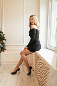 Elegant beautiful girl in fashion black dress with sexy legs and shoes sits near windows
