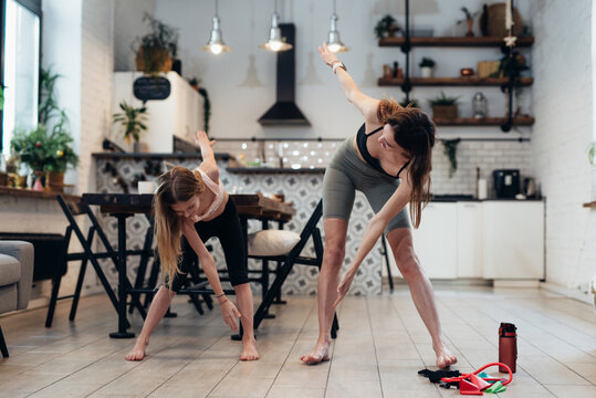 Mother and daughter do sports at home, do standing bends to their toes, twisting their backs