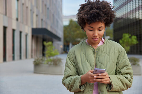 Outdoor shot of curly haired woman with Afro hair holds modern smartphone gadget for networking dressed in casual anorak surfs internet reads good news edits media files does online banking.