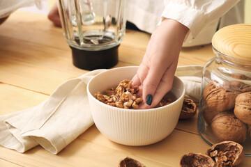 Fototapeta Woman preparing tasty walnut milk on kitchen table, closeup obraz