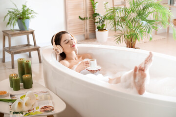 Fototapeta Young woman with headphones and cup of coffee taking bath at home obraz