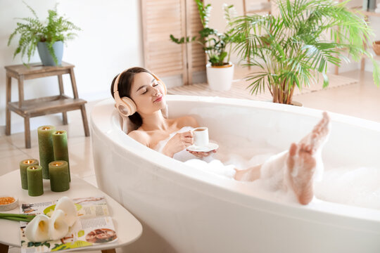 Young woman with headphones and cup of coffee taking bath at home