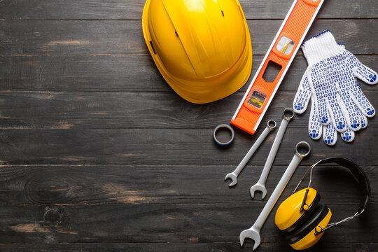 Hardhat with builder's supplies on dark wooden background