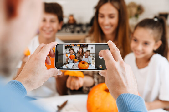 White man taking photo of his family while getting ready for Halloween