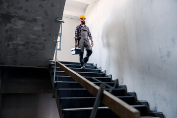 Fototapeta A bearded handyman with a helmet on his head with a toolbox in his hands is going down the stairs in a new building in the building process. There is a lot of work to do. obraz