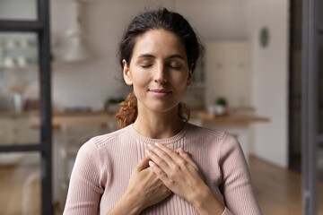 Fototapeta Close up of calm young Caucasian woman hold hands on heart chest feel grateful and thankful. Happy millennial female show gratitude, love and care, pray or visualize. Religion, faith concept. obraz