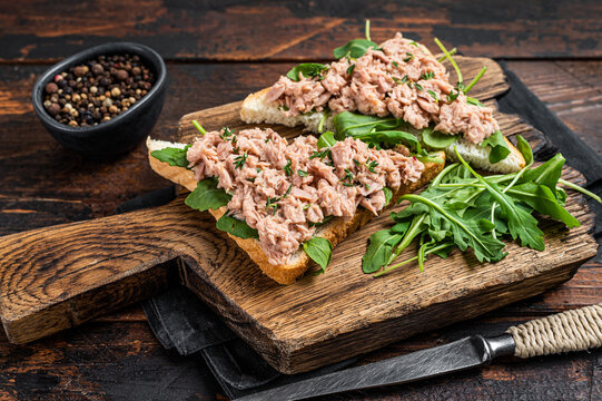 Canned Tuna Toasts or Sandwich with lettuce and arugula. Dark Wooden background. Top view
