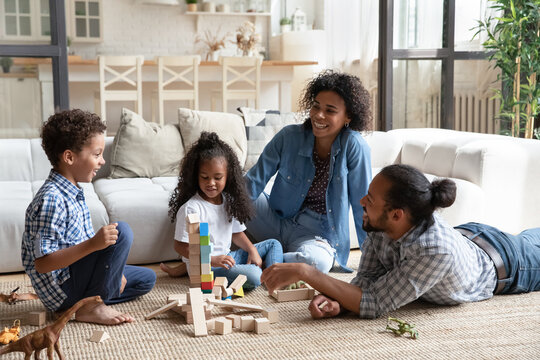Happy African American parents and kids playing with construction toys together, sitting on warm floor in living room, smiling mother and father with little son and daughter spending leisure time
