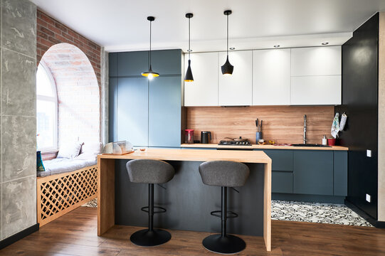 View of contemporary kitchen in white and grey colours. Interrior of studio kitchen with wooden laminate, big window and lot of lampshades. Concept of stylish design.