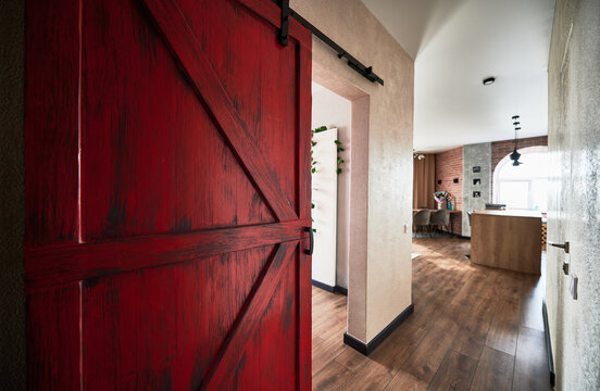 View of big red door to the corridor leading to the kitchen. Interior of appartment in loft style with wooden flooring. Concept of flat decor.