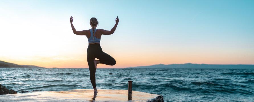 junge attraktive Frau praktiziert Yoga am Meer und macht die Baum Figur