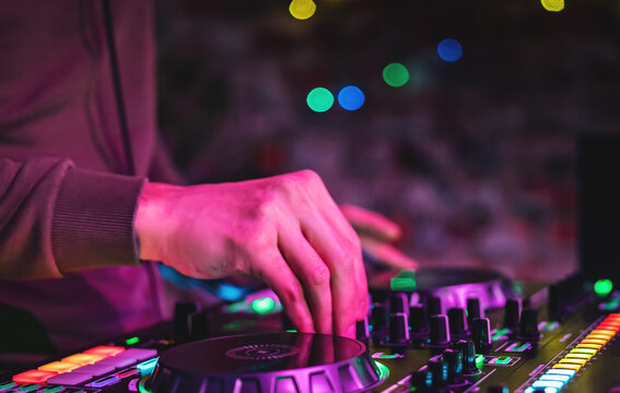 DJ Hands creating and regulating music on dj console mixer in concert nightclub