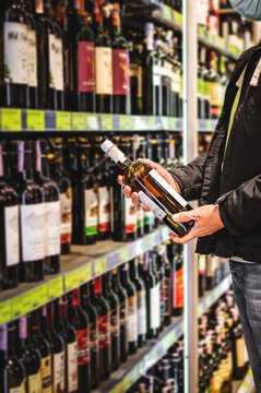 man hand holding bottle wine in grocery store in supermarket