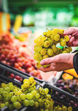 man hand holding grape in grocery store in supermarket
