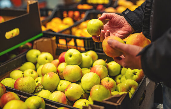 man hand holding apple in grocery store in supermarket