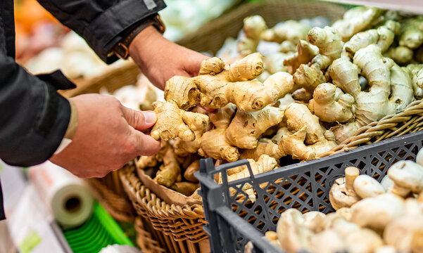 man hand holding ginger root in grocery store in supermarket
