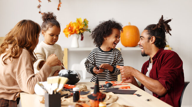 Young joyful african american family mother, father and two kids preparing for Halloween at home