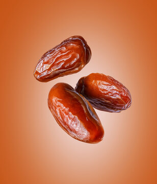 Three dried dates close up in the air