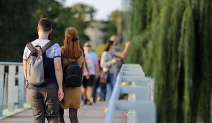 Fototapeta Para młodych ludzie, kobieta i mężczyzna z plecakami spaceruje po moście we Wrocławiu.  obraz