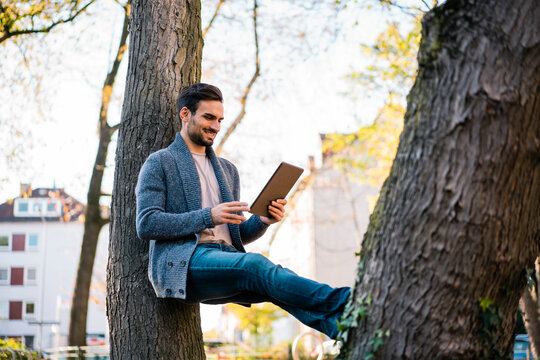 Smiling young man watching video on digital tablet while leaning on tree trunk at park