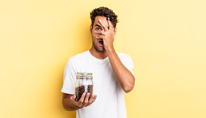 hispanic handsome man looking shocked, scared or terrified, covering face with hand. coffee beans...