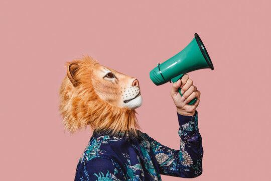 man wearing a lion mask speaks into a megaphone