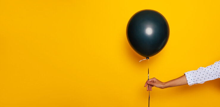 Banner photo of female hand with a helium balloon in Black Friday