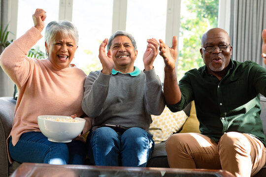 Two happy diverse senior couple and their african american male friend watching tv and having fun