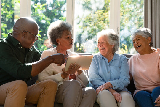 Three happy diverse senior woman and african american male friend sitting on sofa and using tablet
