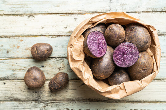Close up of farm fresh purple potatoes in a paper bag on white wooden background, top view
