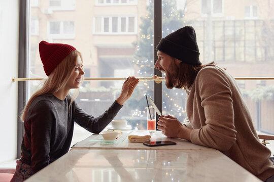 Blonde girl feeding her bearded boyfriend in cafe