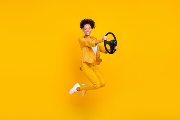 Obraz Full length body size photo woman jumping keeping steering wheel isolated vivid yellow color background - fototapety do salonu